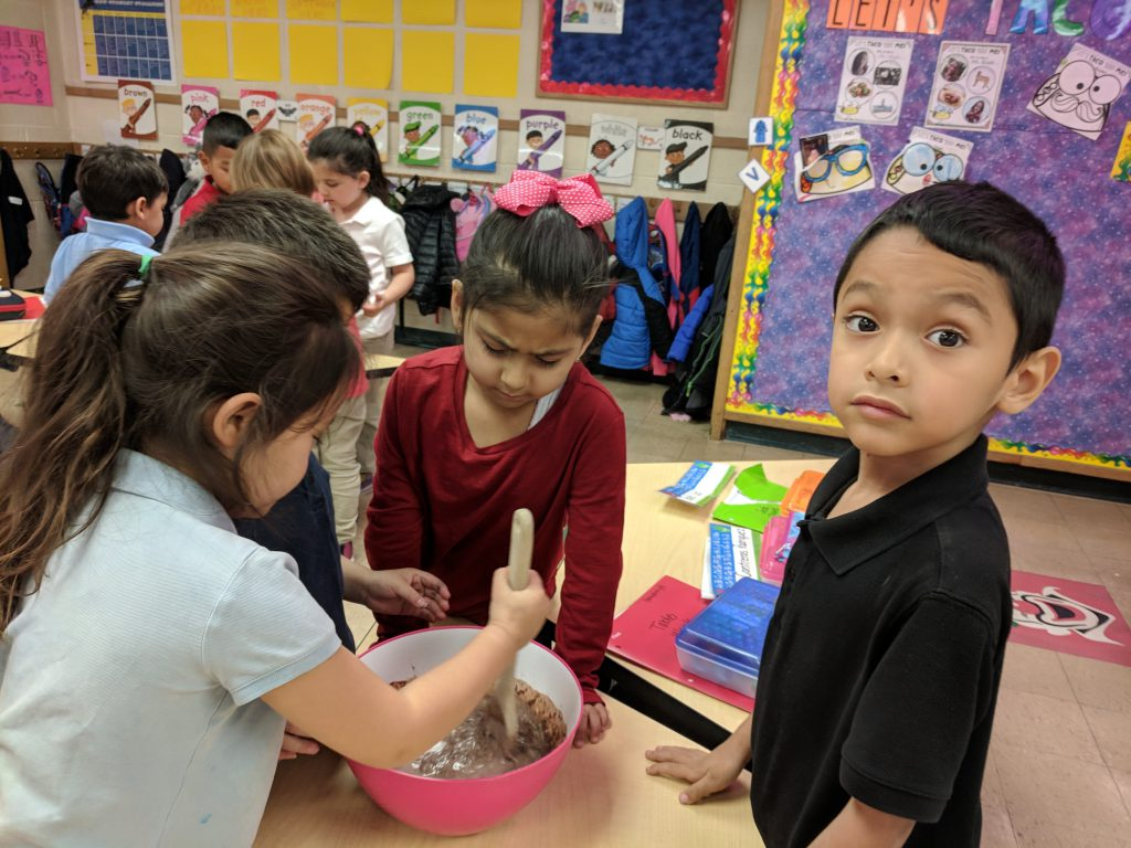 """Kindergarten has been working hard to learn about letters and sounds. Ms. Mayer & Ms. Quaas' class learned about the /p/ sounds with the poem """"Pudding in the Pan."""" We then made pudding to put in our own pans. We also found all of the /p/ sounds in our poem! Photo Credit: Ms. Quaas"""