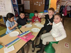 Kindergarten has been working on comparing amounts. We had a snack, but as we set up we realized that the amount of plates, napkins, and drink were not equal to the amount of people. We talked about less than, more than, and equal to. After we made sure everything was equal we enjoyed a snack. Photo Credit: Ms. Quaas