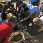 3rd Graders work in the school garden to plant lettuce and cilantro.